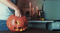 Male hands lights up candle inside jack o lantern then turns off light Halloween Stock Footage