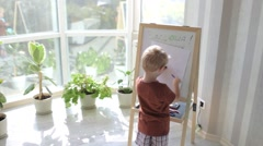 Boy Draws a Marker on the Easel by the Window Stock Footage