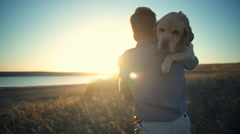 Back view of man carrying old dog in sun light slow motion Stock Footage