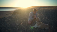 Young man gently caressing old dog in dry grass at sunset Stock Footage