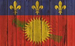 A vignette background image of the flag of Guadeloupe painted onto wooden boa Stock Illustration
