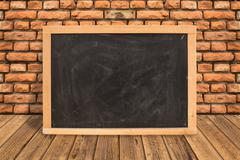 Blank blackboard on diagonal wooden table at red brick wall,Template mock up Stock Photos
