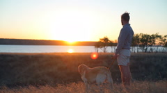 Man and dog enjoying beautiful sunset lanscape Stock Footage