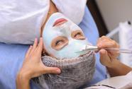 Beautiful woman with facial mask at beauty salon Stock Photos