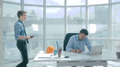 Boss discuss project with employee, gives advice, using digital tablet in new Stock Footage