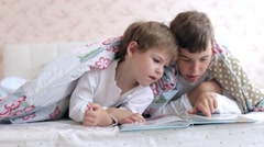 Brothers Read a Book Lying on the Bed Stock Footage