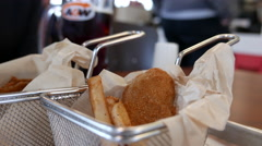 Close up woman putting pepper on fries and chicken strip at A&W restaurant Stock Footage