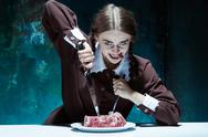 Bloody Halloween theme: crazy girl with a knife, fork and meat Stock Photos