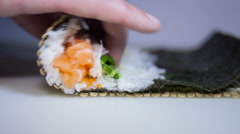 Sushi rolls making process with man's fingers Stock Footage