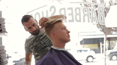 Barber cuts client with scissors in barber shop Stock Footage
