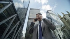 4k, London businessman talking on smartphone, punches the air having just clinch Stock Footage