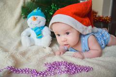Christmas card with cute baby boy weared in santa red hat Stock Photos