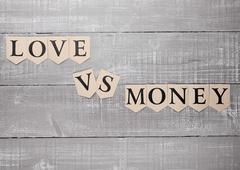 Love vs money paper letters symbol motivation sign on wooden board Kuvituskuvat
