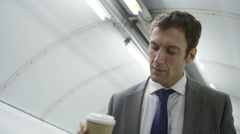 4k, Businessman drinking coffee as he goes up on escalator in underground train  Stock Footage