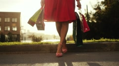 Shopaholic woman in beautiful dress holding many shopping bags walking on the Stock Footage