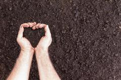 Pair of hands holding soil in heart shape Stock Photos
