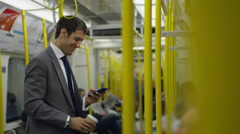 4k Smiling businessman on city subway train, drinking coffee & looking at phone Stock Footage