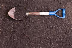 Spade lying on a prepared bed of rich health soil Stock Photos
