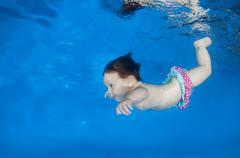 4 months infant learning to swim underwater in waterbaby class in the pool Stock Photos