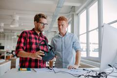 Young men testing virtual reality goggles in office Stock Photos