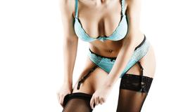 Woman putting on black stockings Stock Photos