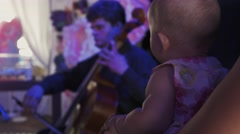 Mother with baby listen performance of musician on celebration event. Concert Stock Footage