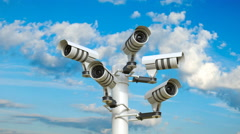 The camera pans five security cameras attached to a pole. Stock Footage