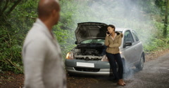 4K Stranded couple with broken down car. Man fed up while woman talks on phone. Stock Footage