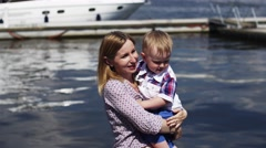 Mother and little son put off shoes at seafront. Event. Summer sunny day. Water Stock Footage