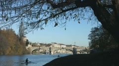 Turin in autumn along the Po river with rowers training and historical bridge Stock Footage