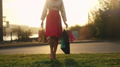 Blurred shopaholic woman in beautiful dress holding many shopping bags walking Stock Footage