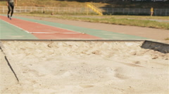 Male athlet makes a long jump at the stadium Stock Footage