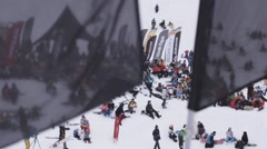 Snowboarders and skiers relax in encamp. Ski resort. Waving flag before camera Stock Footage