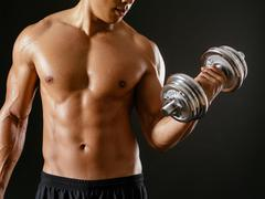 Asian male doing bicep curls Stock Photos