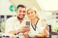 Happy couple taking selfie with smatphone at cafe Stock Photos