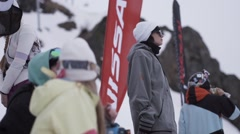 Girl in sunglasses stay in encamp among other people. Ski resort. Waving flags Stock Footage