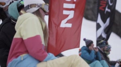 Snowboarders and skiers enjoy event in encamp. Ski resort. Red flags. Couple Stock Footage