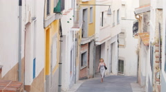 Woman tourist admiring the ancient street in the old town in Spain. It goes down Stock Footage