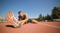 Male athlet stretches his leg at the stadium Stock Footage