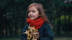 Funny, cheerful cute little girl close-up collects yellow autumn leaves in park Stock Footage