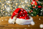 Close up of santa hat on wooden table over lights Stock Photos