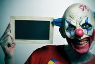 Evil clown with a blank chalkboard Stock Photos
