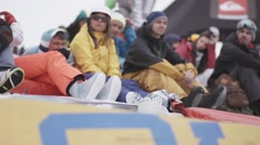 Snowboarders and skiers watching event in encamp. Ski resort. Red waving flags Stock Footage
