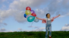 Little girl runs towards the camera holding coloured balloons, in slow motion Stock Footage