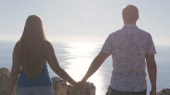 Couple on a date holding hands the background of the ocean solar flare Stock Footage