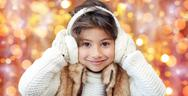 Happy little girl in earmuffs over holidays lights Stock Photos