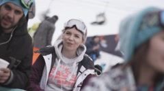 Snowboarders and skiers enjoy event in encamp. Young couple. Ski resort Stock Footage