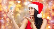 Woman in santa hat taking selfie by smartphone Stock Photos