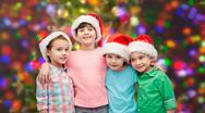Happy little children in santa hats hugging Stock Photos