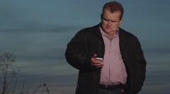 Adult man reading news on the mobile and standing at the evening Stock Footage